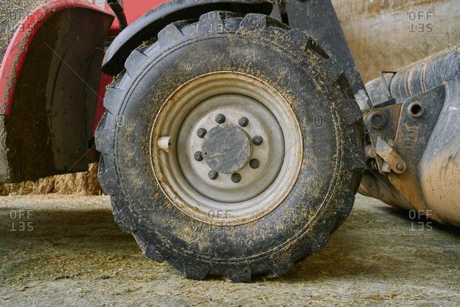 Dirty tractor wheel in garage on farm