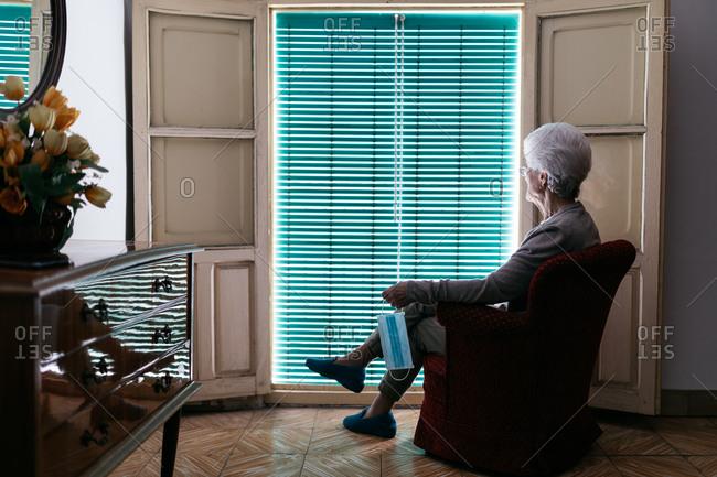 Lonely elderly woman spending day alone during coronavirus outbreak