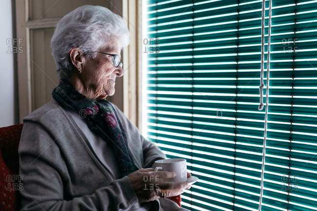 Aged woman with cup of tea staying at home during quarantine