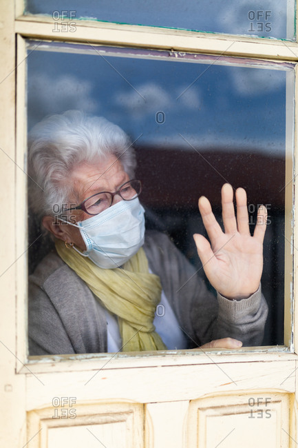 Senior woman in protective mask looking out window