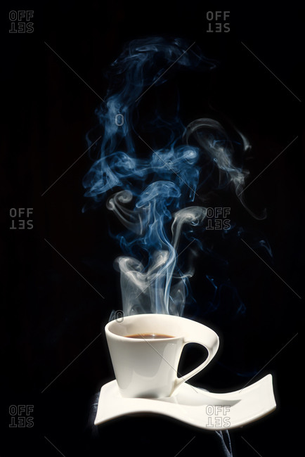 White ceramic cup of fresh hot coffee with steam rising up placed on white ceramic plate in dark room on black background