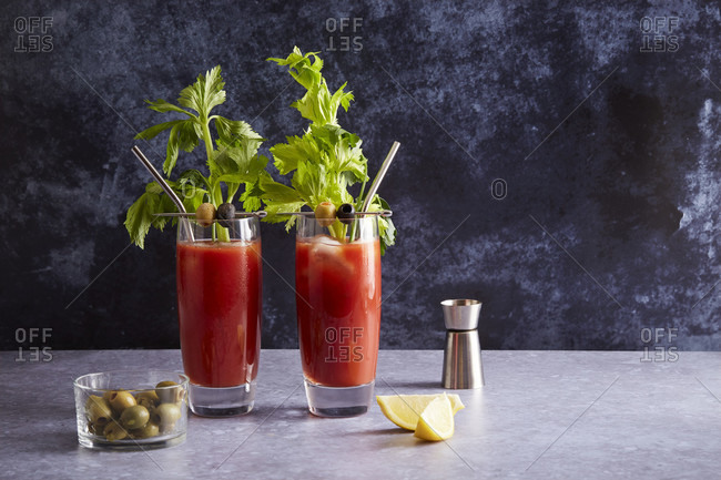Bloody Mary with olives, jigger, and lemon wedge