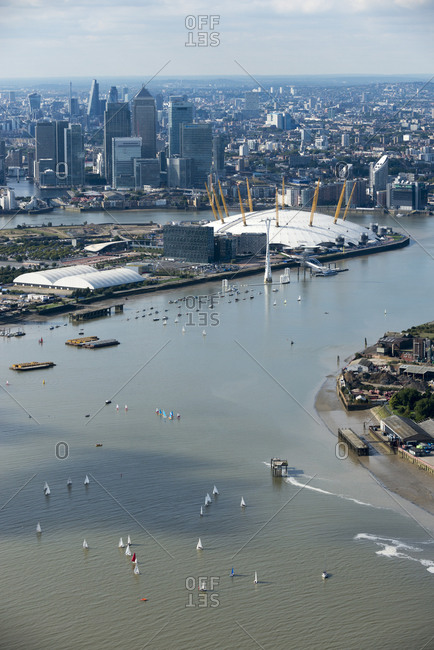 London, United Kingdom - October 6, 2013: An aerial view of sailing dinghies competing in a race on the Thames river near Docklands with views of the O2 and the city in the distance