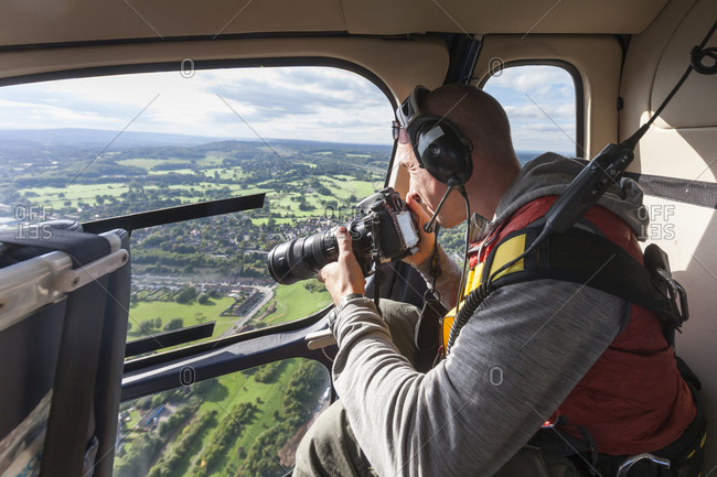 A photographer takes pictures of London from a helicopter