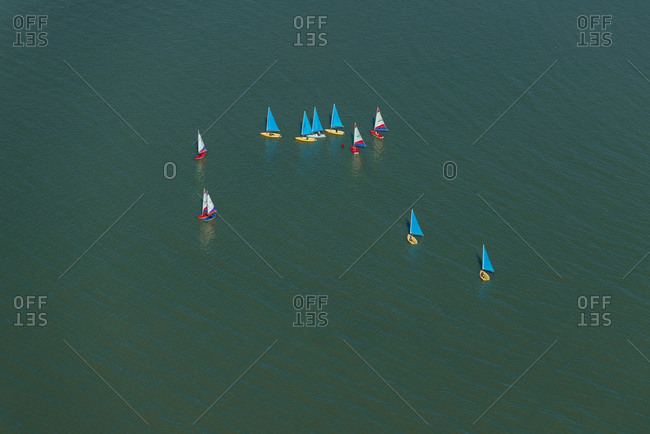 An aerial view of sailing dinghies competing in a race on the Thames river near Docklands