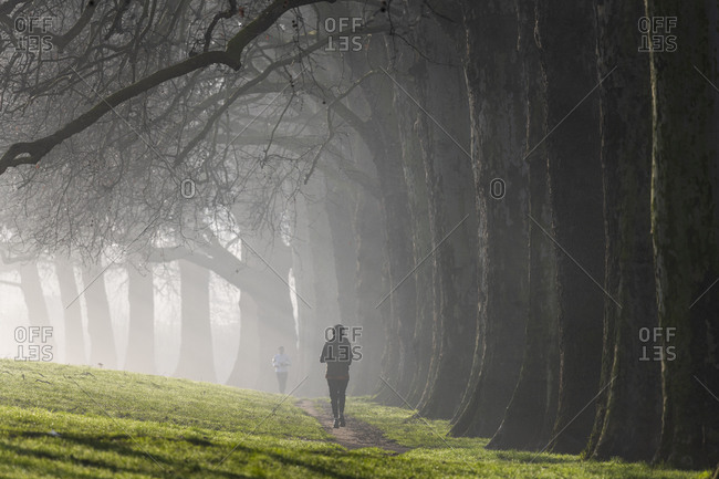 Runners out for a jog in Hackney Downs in London on a misty winter morning