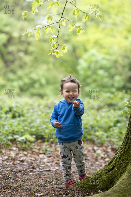 A happy toddler playing in the woods at Hampstead Heath in London