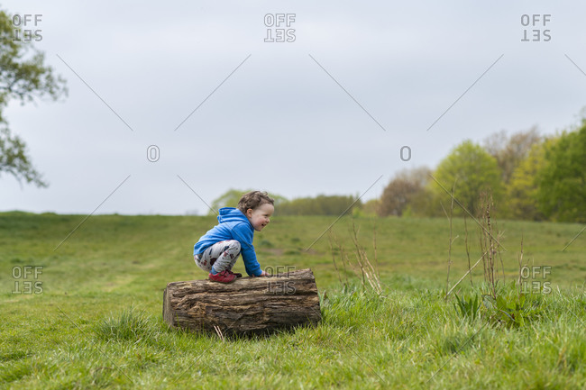 A toddler playing on a log at Hampstead Heath in London