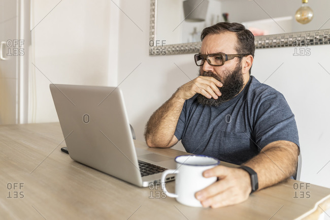 Man with a beard teleworking on his laptop in his apartment, side view, drinking a cup of coffee