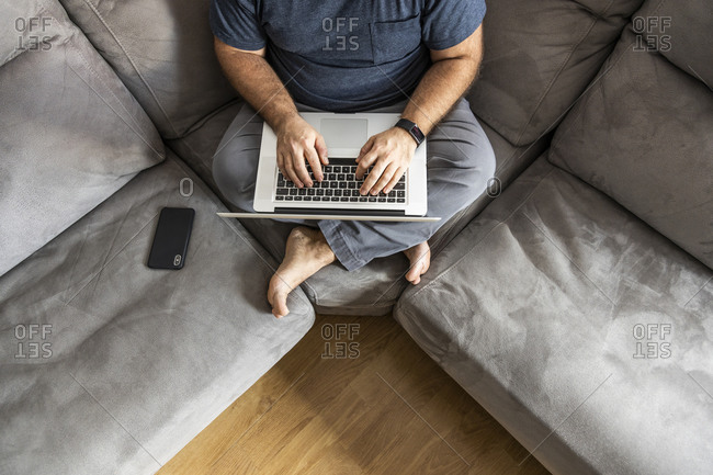 Man teleworking on his laptop and smart phone in his apartment, top view, sitting on the sofa