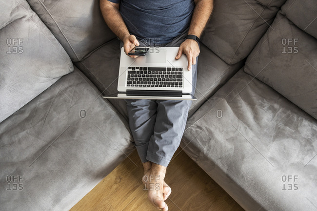 Man with a beard teleworking on his laptop and smart phone in his apartment, top view, sitting on the sofa