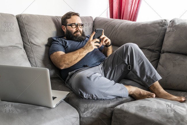 Man with a beard teleworking on his laptop and smart phone in his apartment, side view, sitting on the sofa, checking messages