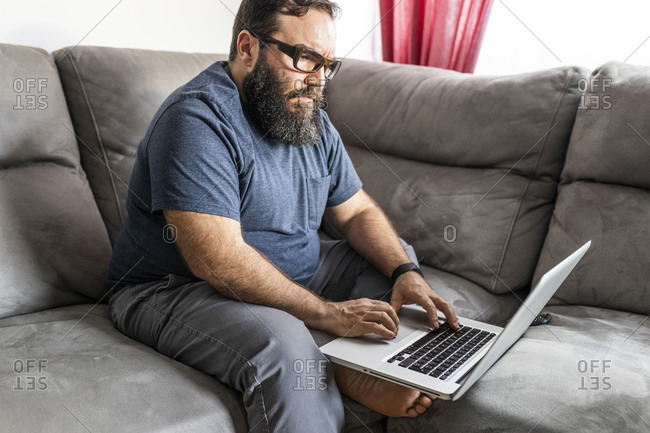 Man with a beard teleworking on his laptop and smart phone in his apartment, side view, sitting on the sofa