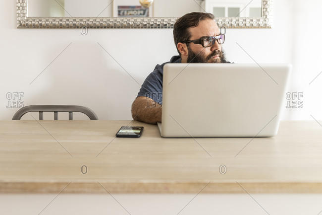 Man with a beard teleworking on his laptop in his apartment, front view