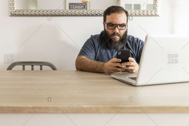 Bearded man teleworking at home, chatting on his smart phone, front view