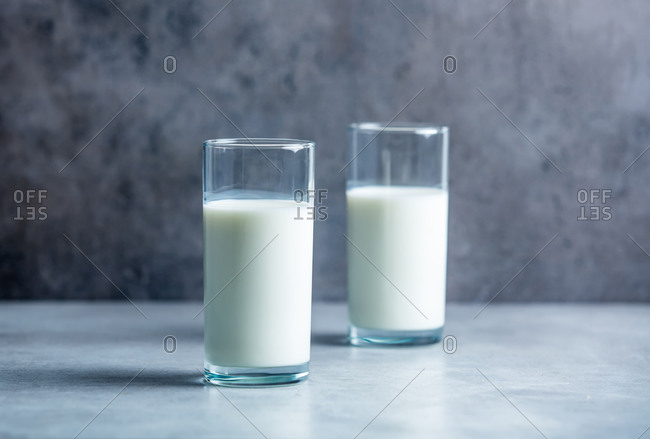 Two glasses of milk on a grey background