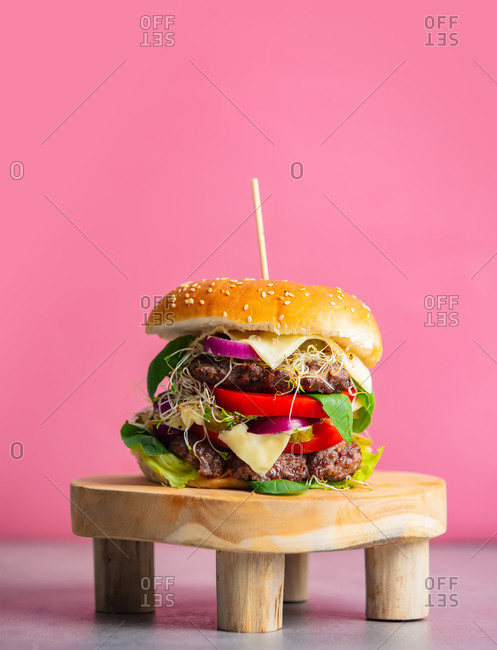 Home-made burger with meat and cheese on stand on pink background