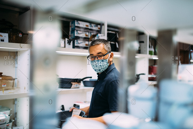 Asian man shopping in a store while wearing a facemask