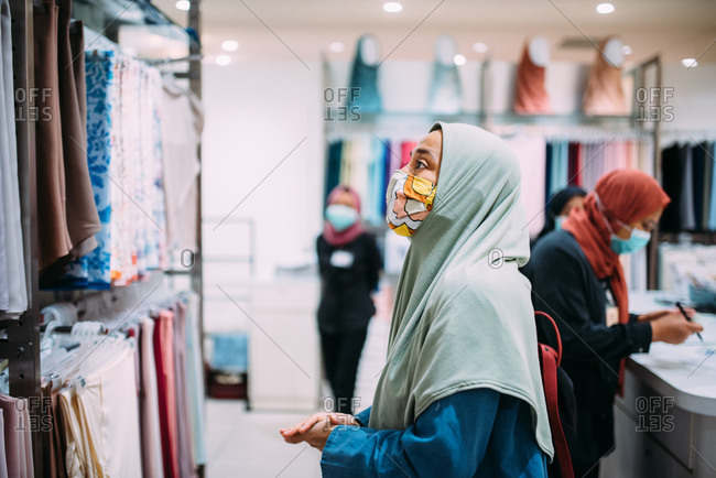 Asian woman in a store wearing a facemask