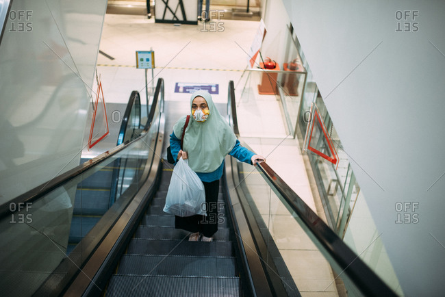 Asian woman wearing a facemask while riding on shopping mall escalator