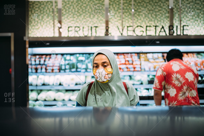 Asian woman shopping in a grocery store wearing a facemask