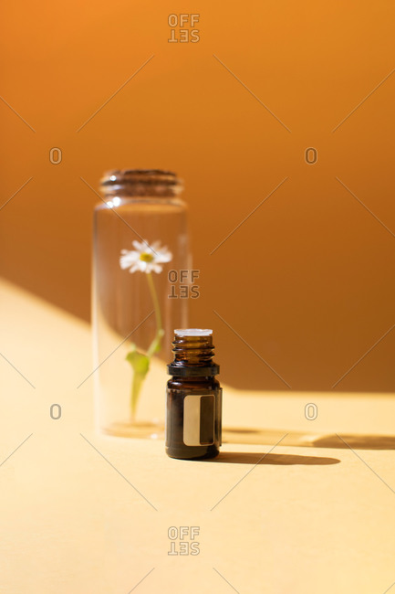 Vial of essential oil with a daisy flower in a jar on yellow background