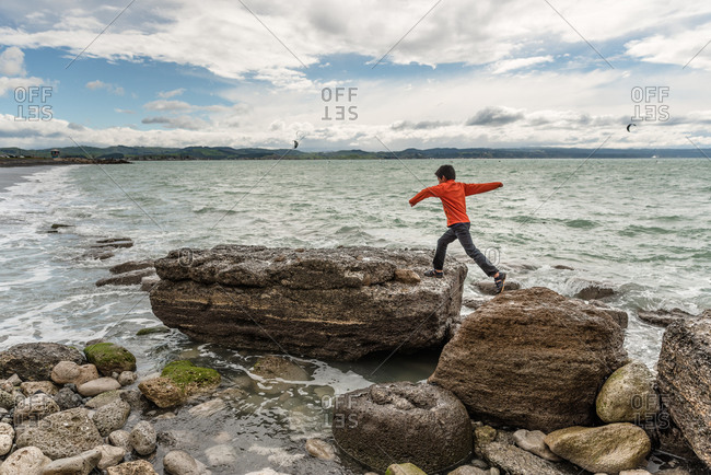 Boy jumping from one large rock to another on a beach in Hawke's Bay, New Zealand