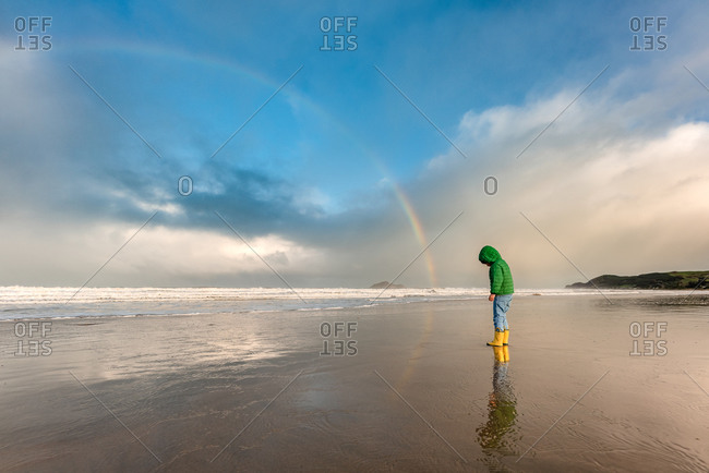 Child on a beach in Hawke's Bay, New Zealand with rainbow in the sky