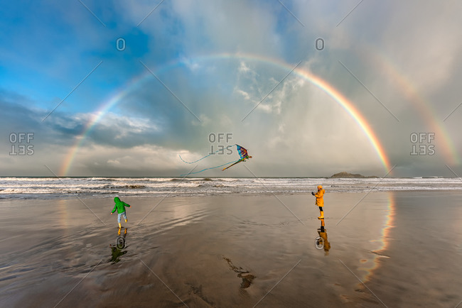 Two children on a beach flying a kite under dramatic rainbow filled sky