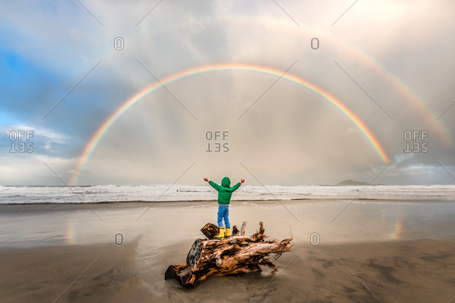 Young child standing on driftwood under a double rainbow on the beach