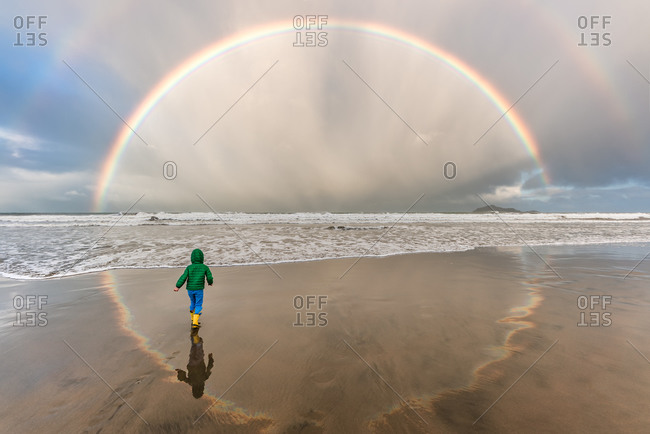 Young child walking on beach under a double rainbow