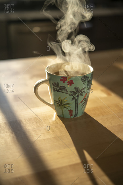 Morning coffee in a tropical mug with steam