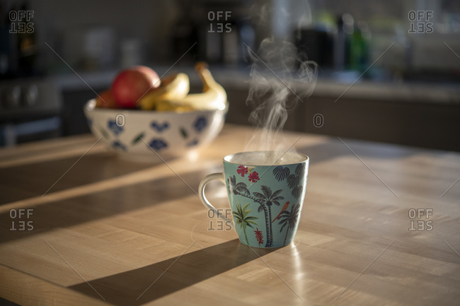 Morning coffee in a tropical mug with steam on a wooden table