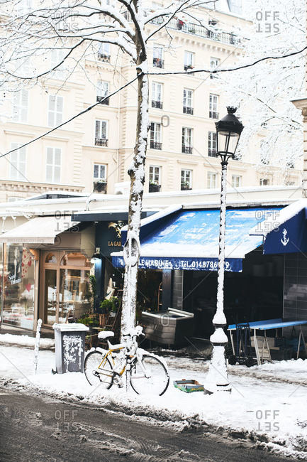 Paris, France - February 7, 2018: Snow covered city street scene with bicycle by a tree