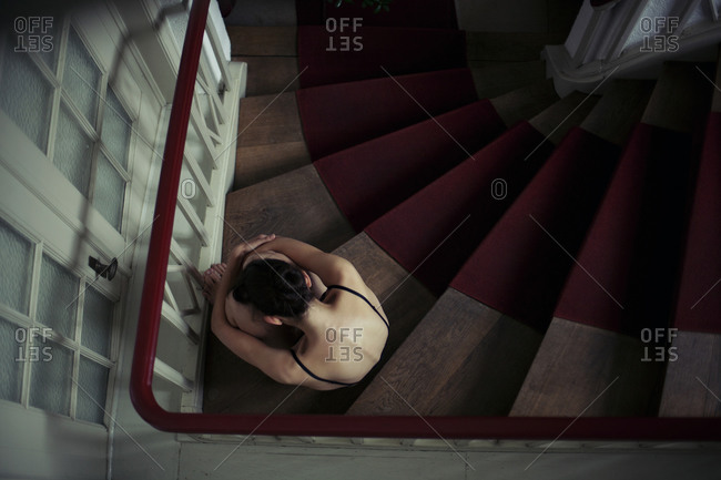Half-naked woman sitting huddled on the stairs