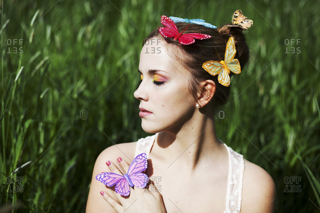 Young woman with closed eyes and artificial butterflies