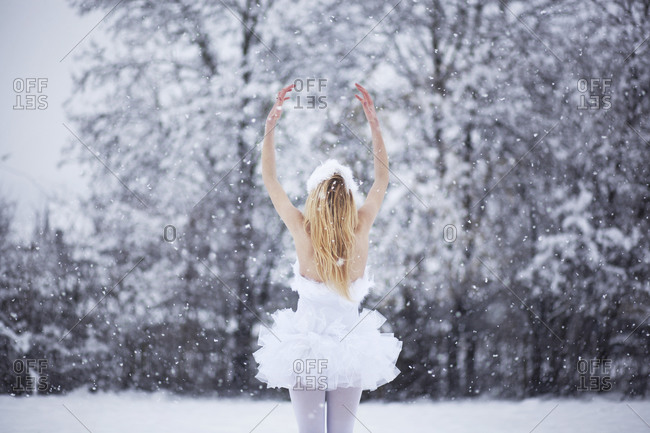 Ballerina sitting on a ledge covered in snow
