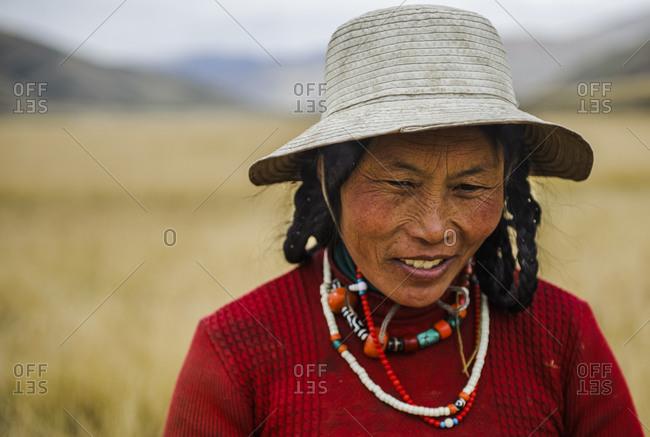 A Tibetan nomad woman taking a break in the field