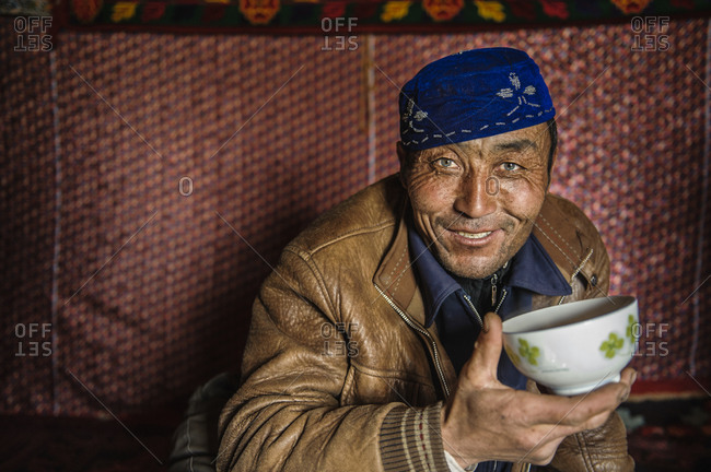 Uighur man with emerald green eyes holding a bowl in remote Xinjiang