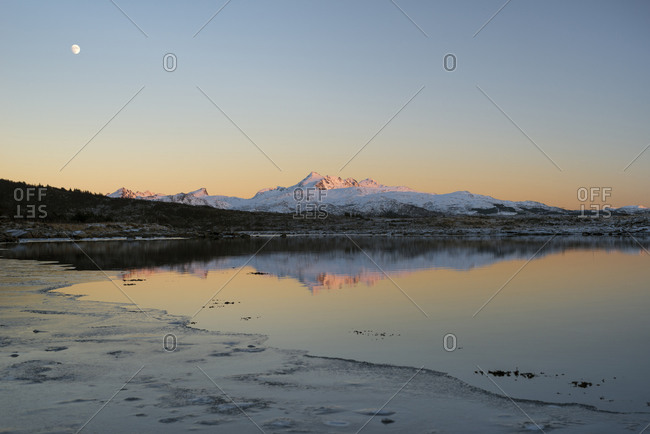 Mountains in the evening light reflected in a lake while the moon is in the sky, Lofoten, Nordland, Norway