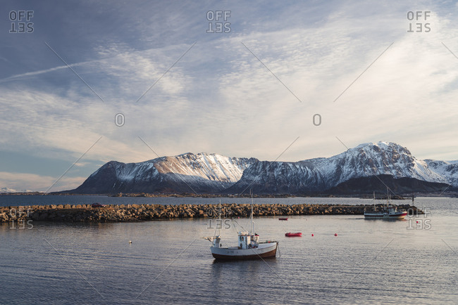 Fishing boats drift near the shore in the soft light of the soon setting sun, Eggum, Lofoten, Nordland, Norway