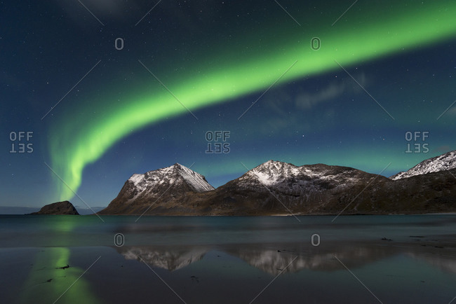 Northern Lights as a closed band over the summit of Mannen and Haukland Strand, Lofoten, Nordland, Norway