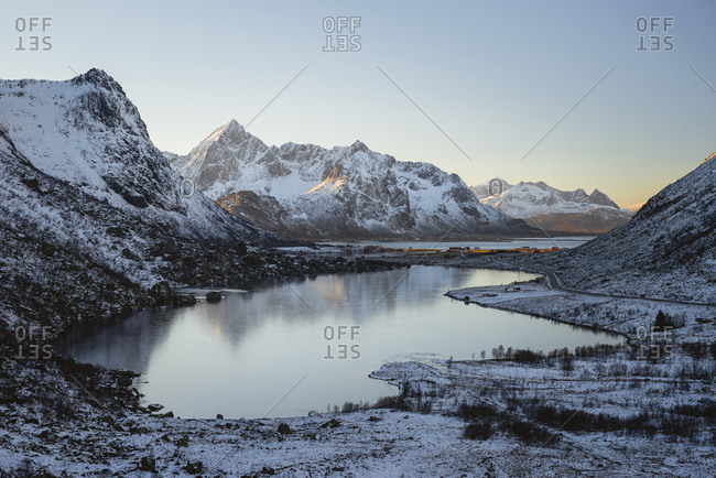 Frozen lake reflects the sunlit peaks of the mountains in the background, Lofoten, Nordland, Norway