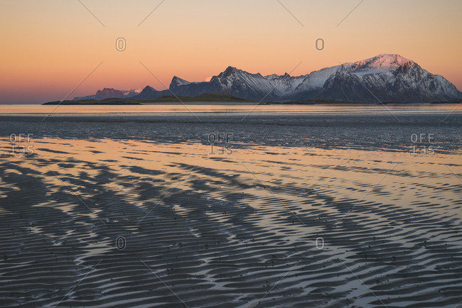 Delicate colors of the sunset are reflected in the puddles on the beach at low tide, Lofoten, Nordland, Norway