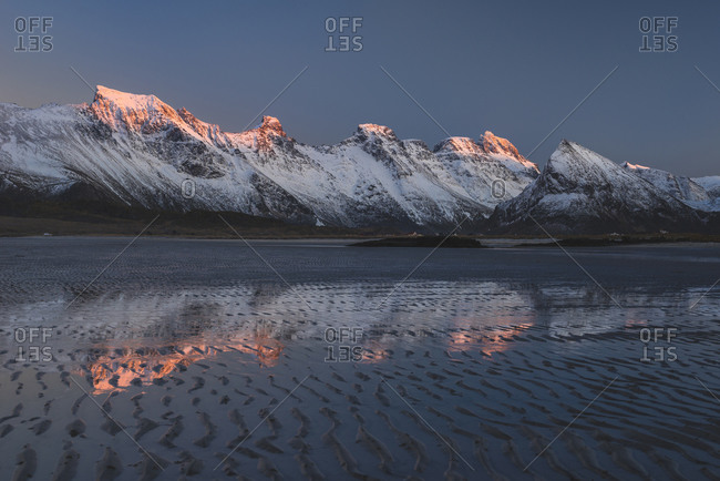 Last light on the mountain peaks is reflected in the puddles on the beach at low tide, Lofoten, Nordland, Norway