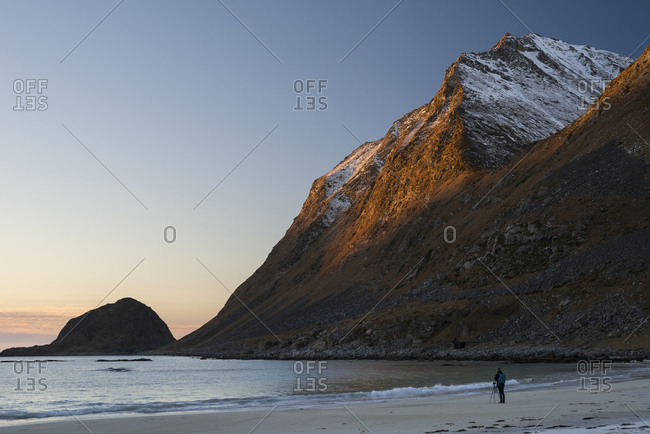 Photographer at Haukland Beach taking pictures of the last sunrays on Veggen, Lofoten, Nordland, Norway