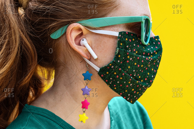 Side profile of a young red-haired woman wearing a green mask and teal sunglasses on a solid yellow background