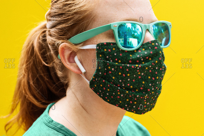 A young red-haired woman wears a green mask, teal sunglasses, and white earphones on a solid yellow background