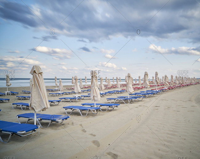 Empty red and blue sun loungers on an empty beach with umbrellas