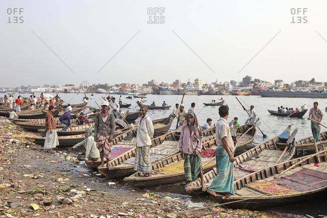 Dhaka, Bangladesh - April 27, 2013: Boatmen lined up waiting for passengers at Sadarghat Boat Terminal